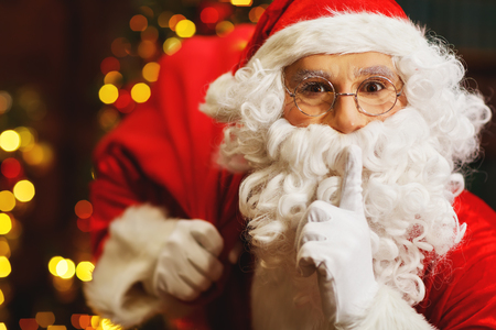 Santa Claus with a bag of gifts at the Christmas tree Stock Photo
