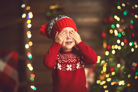 miracle: little girl closed eyes  her hands in anticipation of a Christmas miracle and a gift Stock Photo
