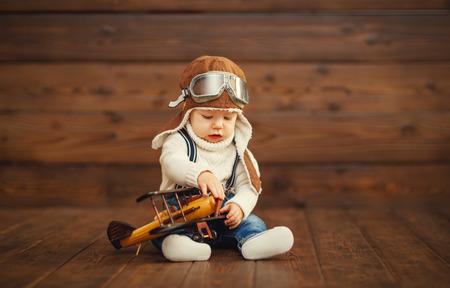 Funny baby boy Pilot Flieger mit dem Flugzeug auf hölzernen Hintergrund lachen Standard-Bild - 65640837