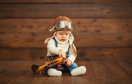 funny baby boy proef vliegenier met vliegtuig lachen op houten achtergrond Stockfoto