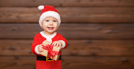 christmas funny: Happy baby in a Christmas costume Santa Claus with gifts on wooden background Stock Photo