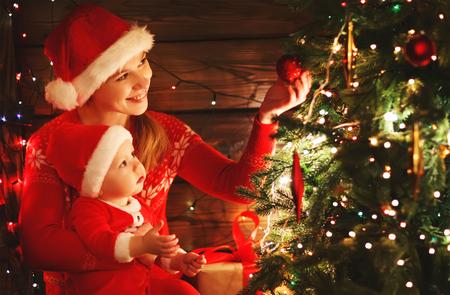baby near christmas tree: happy family mother and baby near Christmas tree in the holiday night