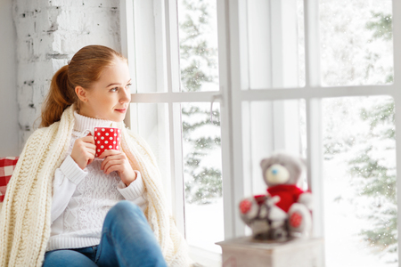 happy young woman with cup of hot tea in winter window Christmas morning
