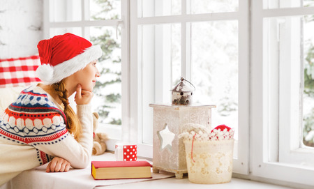 christmas tea: happy young woman with cup of hot tea and book in winter window Christmas morning