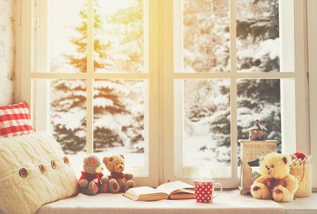 本、熱いお茶のカップとテディベアとクリスマス冬のウィンドウ