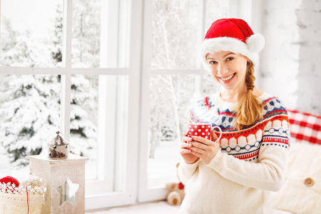 winter window: happy young woman with cup of hot tea in winter window Christmas morning