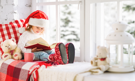 happy child girl reading a book while sitting at a winter window Christmas Stock Photo