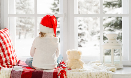happy child girl sitting back in the winter window Christmas