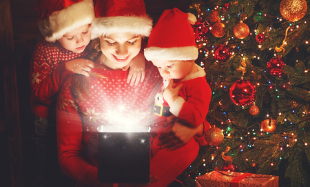 baby open present: happy family on Christmas Eve. mother and children discover a magical gift at the tree