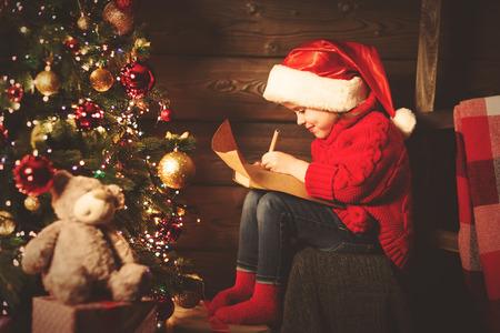 glückliches Kind Mädchen schreibt Brief an den Weihnachtsmann am Weihnachtsbaum am Abend Standard-Bild