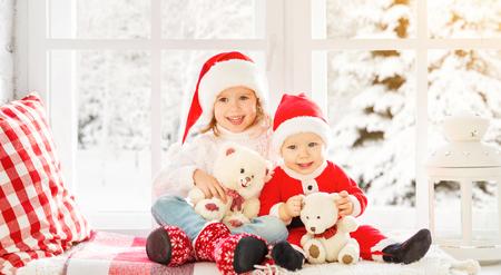 hombre rojo: feliz hermano y hermana niños de la familia riendo y sentado en la ventana de invierno de Navidad