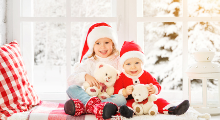 happy family children brother and sister laughing and sitting on the winter window Christmas