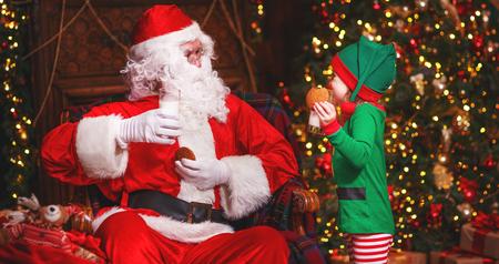 tomando leche: Santa Claus y un niño duende en una leche de consumo y comer galletas de Navidad