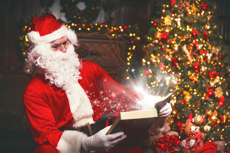 De Kerstman bij Kerstmis met gloeiende magische boek
