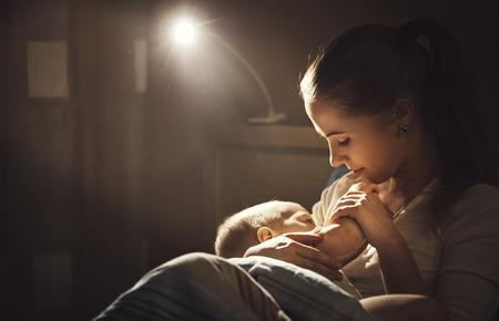 모유 수유. 어머니는 침대 어두운 밤에 아기의 모유 수유
