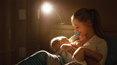 breastfeeding. mother feeding a baby breast in bed dark night Stok Fotoğraf - 66375484