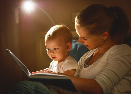 mother and baby sonreading a book in bed before going to sleep Stockfoto