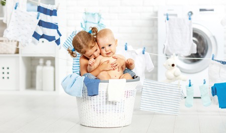 clean clothes: little helpers funny kids happy sister and brother in the laundry to wash clothes, playing and laughing