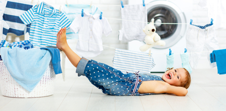 child fun happy little girl  to wash clothes and laughs in the laundry room Stock Photo
