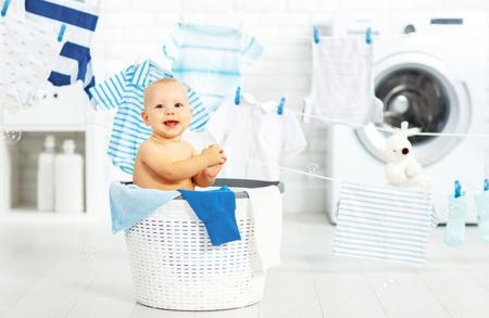 재미 행복한 아기 소년 세탁 방에서 옷과 웃음을 씻어