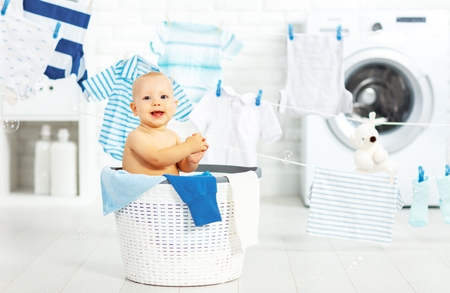 fun happy baby boy  to wash clothes and laughs in the laundry room 版權商用圖片
