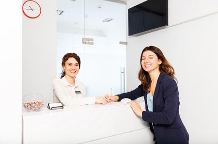 vriendelijke jonge vrouw achter de receptie beheerder met bezoeker klant Stockfoto