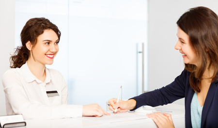 顧客の訪問者とレセプション デスク管理者の背後にあるフレンドリーな若い女性