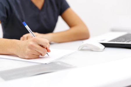 デスクトップ上のコンピューターの横にある紙の上にペンを書くビジネスの女性を手します。