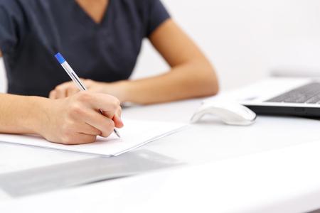 책상에 컴퓨터 옆에 종이에 펜을 작성하는 손 비즈니스 여자