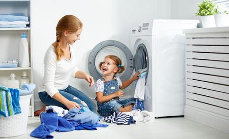 Familie Mutter und Kind Mädchen kleiner Helfer in Waschraum in der Nähe von Waschmaschine und schmutzige Kleidung Standard-Bild - 66956956