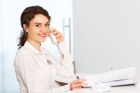 friendly young woman behind the reception desk administrator 版權商用圖片 - 67027789