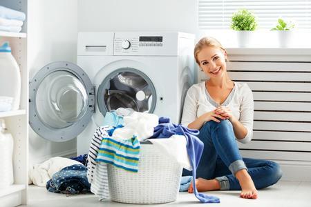 Glückliche Frau Hausfrau in der Waschküche in der Nähe der Waschmaschine mit schmutzigen Kleidern Standard-Bild - 67420720