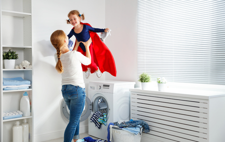 family mother and child girl little superhero helper in laundry room near washing machine and dirty clothes