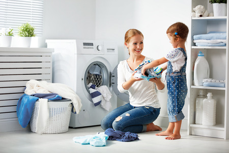 Madre de familia y niña niño pequeño ayudante en la lavandería cerca de la lavadora y la ropa sucia Foto de archivo - 67420719