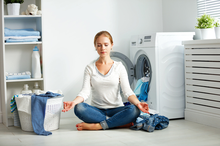 concept. tired housewife meditates in lotus position in laundry room near washing machine and dirty clothes  Stock fotó
