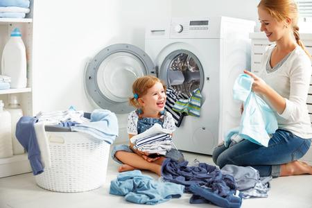 家族の母と子の女の子ランドリー洗濯機と汚れた服の近くに小さなヘルパー 写真素材 - 67410669