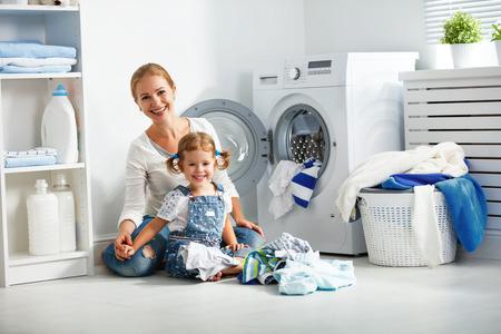 가족 어머니와 자식 소녀 세탁기와 더러운 옷 근처 세탁실에서 작은 도우미 스톡 콘텐츠