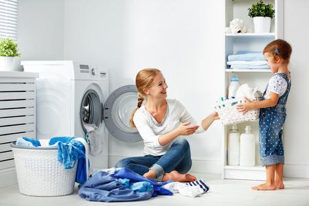 Familie Mutter und Kind Mädchen kleiner Helfer in Waschraum in der Nähe von Waschmaschine und schmutzige Kleidung Standard-Bild - 69377827