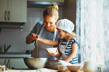 台所での幸せな家族。生地、クッキーを準備する母と子の娘