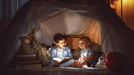 children boy and girl reading book with flashlight in  tent at night  Reklamní fotografie