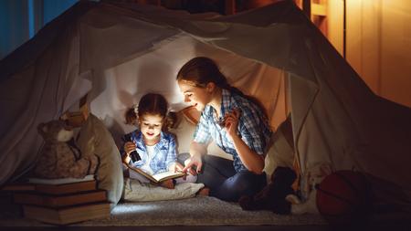 子供のテントの中で読書と家族ゲーム。本と寝る前に懐中電灯を持つ母と子の娘