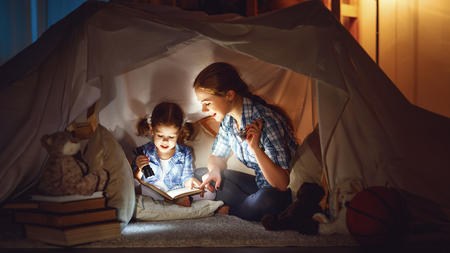 reading and family games in childrens tent. mother and child daughter with  book and flashlight before going to bed  Stok Fotoğraf