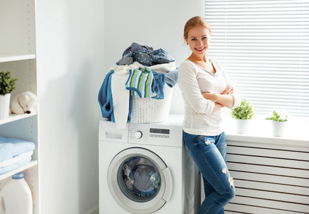 happy woman housewife in the laundry room near the washing machine with dirty clothes Reklamní fotografie
