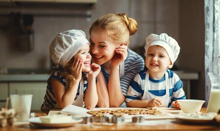 부엌에서 행복 한 가족입니다. 어머니와 반죽을 준비하는 아이들, 쿠키를 구워 스톡 콘텐츠