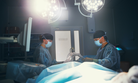 operation lamp: Doctor and assistant preparing for surgery in the dark operating room with a dark lamp