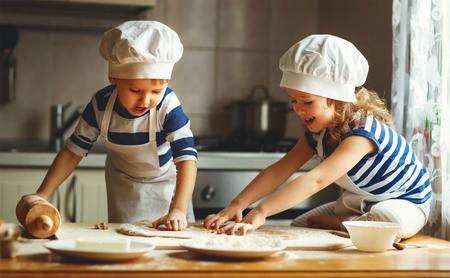 niños divertidos de la familia feliz están preparando la masa, hornear galletas en la cocina Foto de archivo