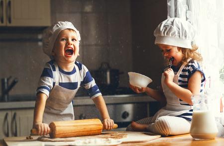 glückliche Familie lustige Kinder bereiten den Teig, backen Kekse in der Küche
