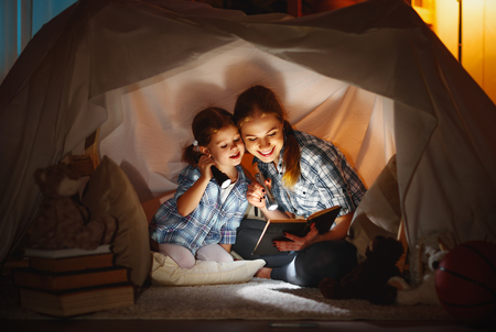 reading and family games in childrens tent. mother and child daughter with  book and flashlight before going to bed