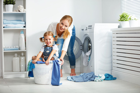 family mother and child girl little helper in laundry room near washing machine and dirty clothes Stock fotó - 70182683