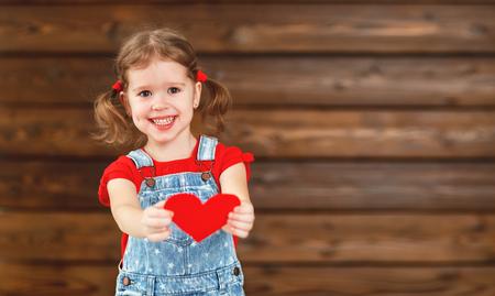 gelukkig lachend kind meisje met hart Valentijnsdag, houten achtergrond